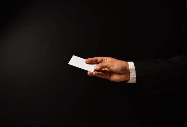 Die hand des geschäftsmannes mit leerer visitenkarte