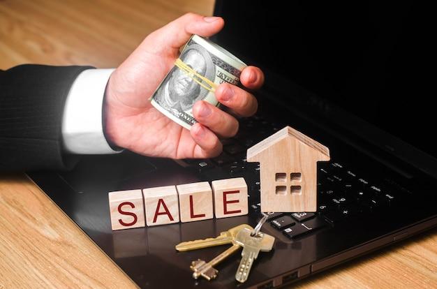 Die hand des immobilienmaklers hält ein bündel geld mit den schlüsseln am haus.
