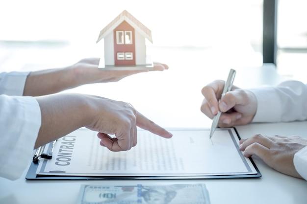 Die hand des immobilienmaklers zeigt und erklärt dem käufer den geschäftsvertrag, die miete, den kauf, die hypothek, ein darlehen oder die hausversicherung.