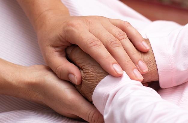 Die hand des jungen mädchens berührt und hält die faltigen hände einer alten frau.