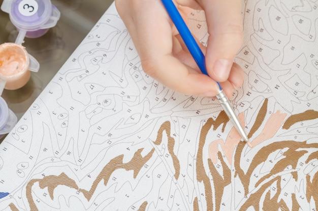 Die hand des jungen mädchens zeichnet mit einem pinselanstrich durch zahlen auf segeltuch