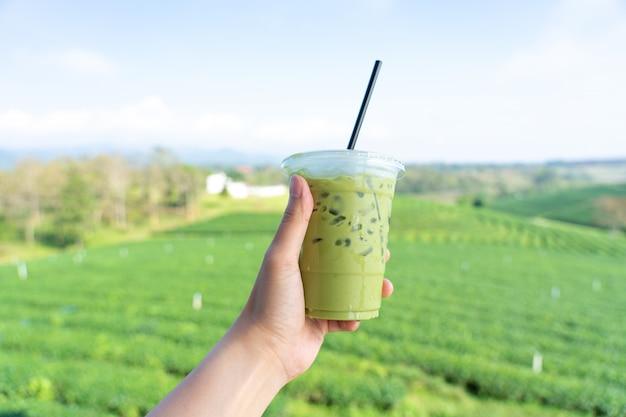 Die hand des jungen mannes, die ein glas getränk des grünen tees hält, archiviert mit einer großen teeplantage