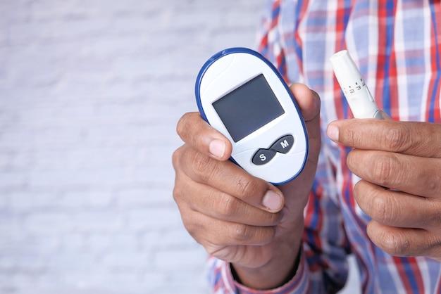 Die hand des jungen mannes misst den glukosespiegel zu hause.