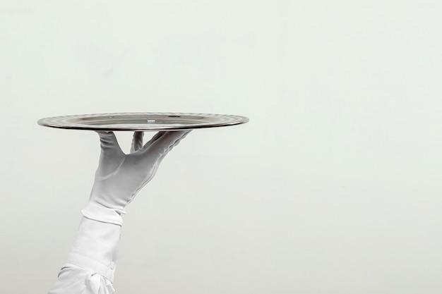 Die hand des kellners in weißen handschuhen hält ein silbernes tablett.