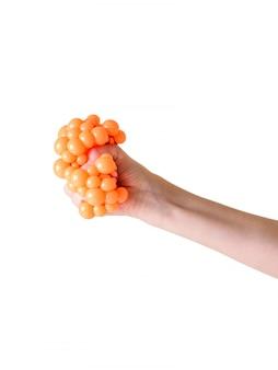 Die hand des kindes drückt spielzeug gegen den druck zusammen, der auf weiß lokalisiert wird.