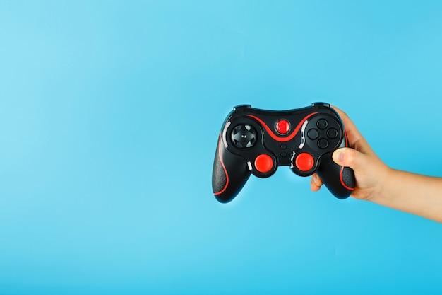 Die hand des kindes hält triumphierend das gamepad auf einer blauen oberfläche