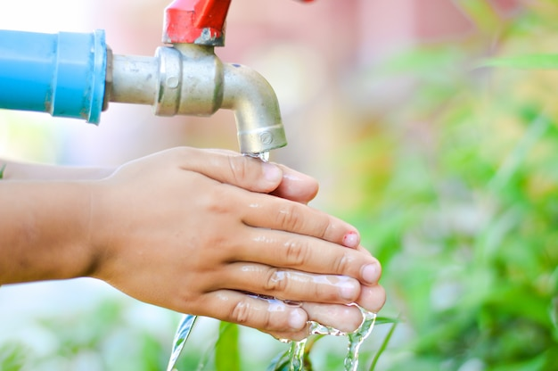 Die hand des kindes ist unter der blauen leitung, konzept ist handwäsche für gute hygiene.
