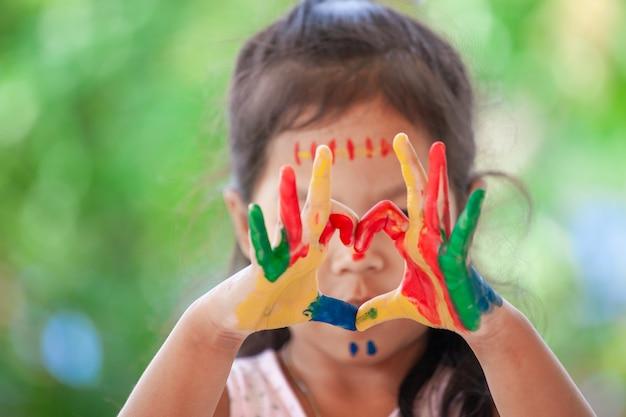 Die hand des kindes mit gemaltem buntem aquarell machen herzform auf grünem naturhintergrund