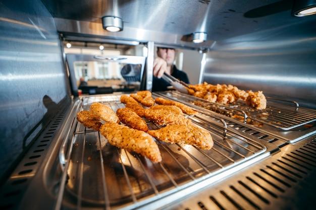 Die hand des küchenchefs nimmt knusprige hühnernuggets nahaufnahme in einem restaurant