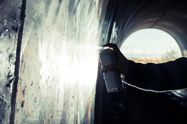 Die hand des künstlers, die graffiti mit aerosoldose auf wand malt