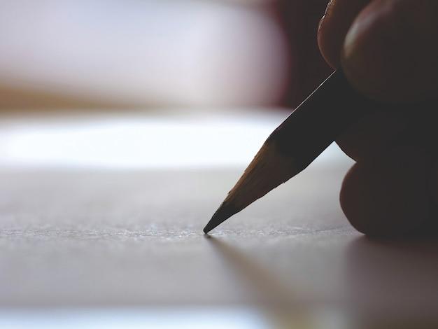 Die hand des künstlers, die mit einem einfachen bleistift, nahaufnahme skizziert oder schreibt