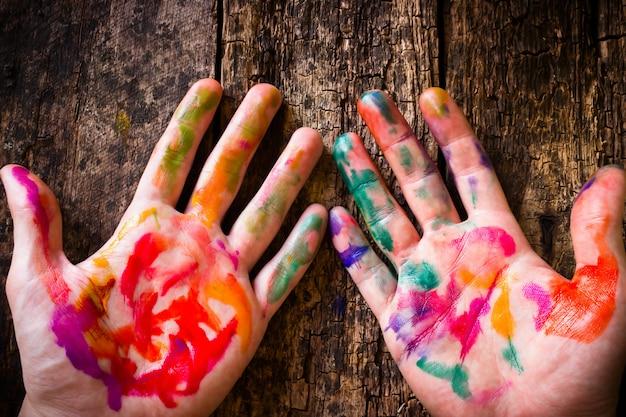 Die hand des künstlers in befleckter farbiger aquarellfarbe an eines holztischs
