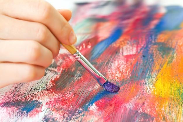 Die hand des künstlers malt auf leinwand.