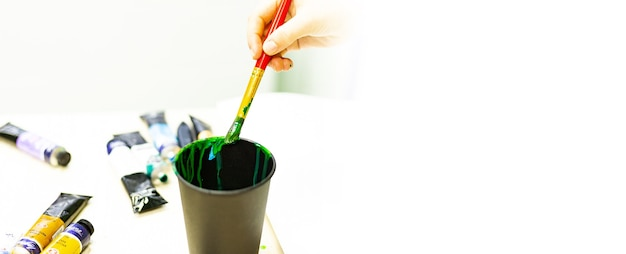 Die hand des künstlers wäscht einen pinsel mit farben in einem glas wasser, ein künstlerwerkzeug, kreativität, zeichnen, zeichentraining, kunstschule, banner.