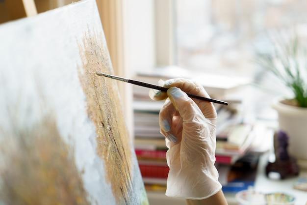 Die hand des künstlers zeichnet nahes hohes des ölgemäldes