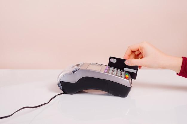 Die hand des kunden in der nähe der bar bezahlt per kreditkarte per terminal, ansicht des handgeräts