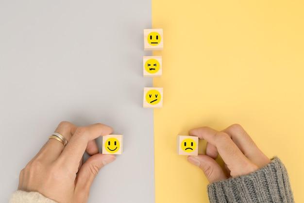 Die hand des kunden wählt emotionen für feedback im geschäft