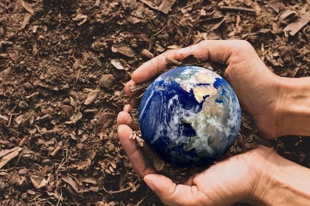 Die hand des landwirts hielt eine kleine blaue welt in seinen händen, die auf dem boden ruhte, earth day concept, elemente dieses von der nasa bereitgestellten bildes.
