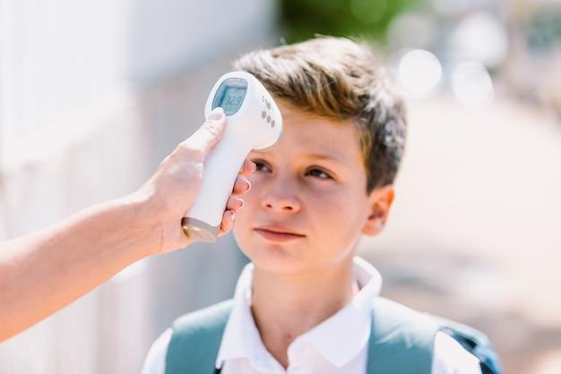 Die hand des lehrers misst die temperatur eines kindes beim betreten der schule mit einem elektronischen thermometer, wobei der kopf des schülers unscharf ist. covid-19- und virus-pandemie-konzept
