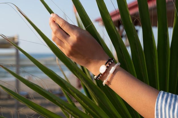 Die hand des mädchens hält das grüne blatt. foto in hoher qualität