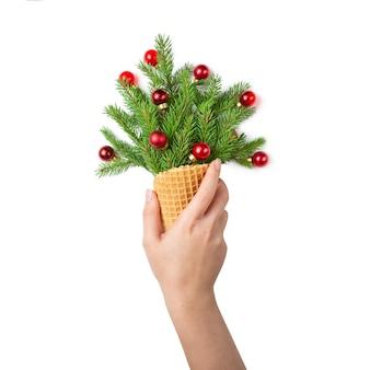 Die hand des mädchens hält eine eistüte mit tannenzweigen und rotem weihnachtsspielzeug.