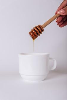 Die hand des mädchens hält einen honigschöpflöffel auf einer weißen tasse