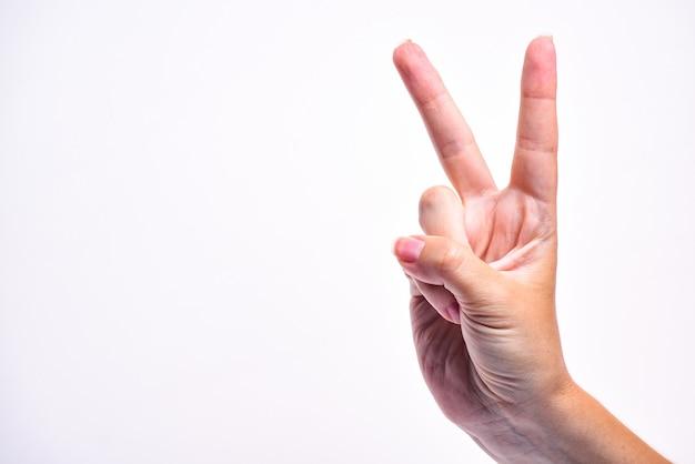 Die hand des mädchens zeigt eine siegeshand. symbol des sieges. hand isoliert. speicherplatz kopieren