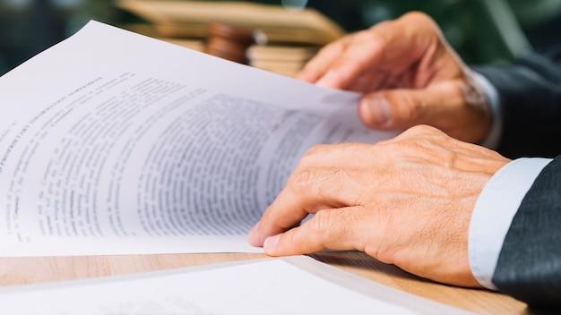 Die hand des männlichen anwalts, die dokument auf schreibtisch im gerichtssaal hält