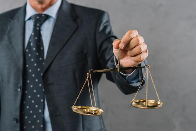 Die hand des männlichen anwalts, die gerechtigkeitskala gegen grauen strukturierten hintergrund zeigt