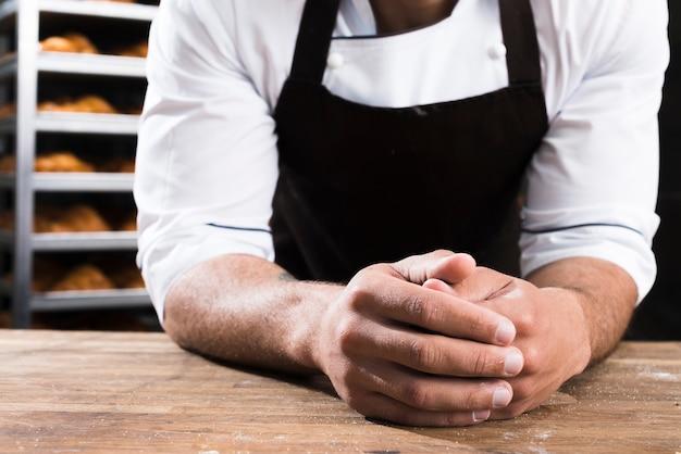 Die hand des männlichen bäckers, die auf holztisch sich lehnt