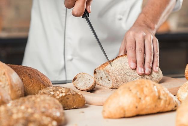 Die hand des männlichen bäckers, die brot mit scharfem messer schneidet