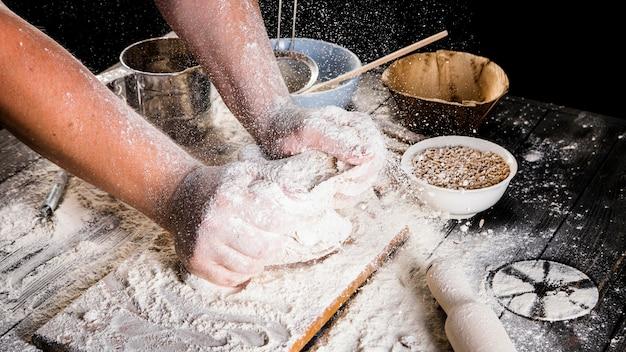 Die hand des männlichen bäckers, die den teig auf dem küchentisch knetet