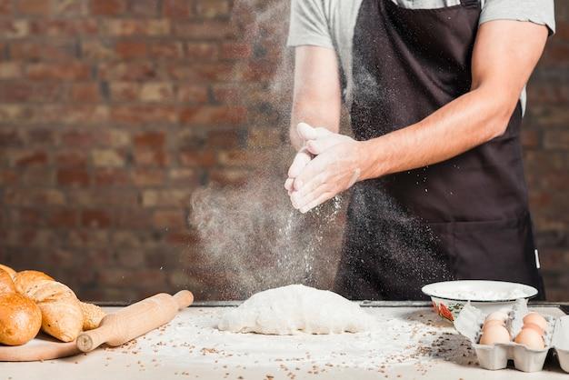 Die hand des männlichen bäckers, die mehl auf geknetetem teig über der küche worktop stäubt