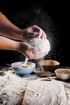 Die hand des männlichen bäckers, die teig für brot vorbereitet