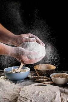 Die hand des männlichen bäckers, die teig mit mehl abwischt