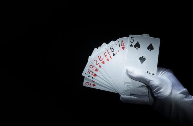 Die hand des magiers, die aufgelockerte spielkarten gegen schwarzen hintergrund hält