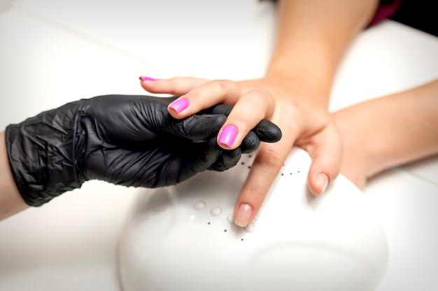 Die hand des maniküre-meisters hält einen weiblichen finger mit lila nagellack, während die nägel in einem nagelstudio gemalt werden