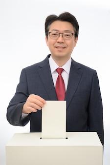Die hand des mannes den stimmzettel in der wahlurne hinunter.