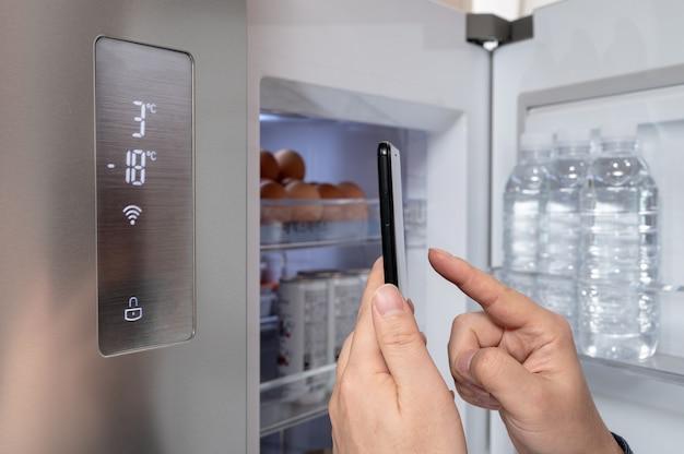 Die hand des mannes, der mit seinem smartphone den kühlschrank steuert. internet der dinge konzept.