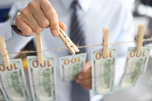 Die hand des mannes des geschäftsmannes befestigt fmerikanische dollars am seil mit wäscheklammern nahaufnahme. geschäftsgeldwäschekonzept.