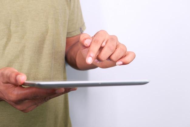 Die hand des mannes, die auf digitalem tablett lokalisiert in weiß arbeitet