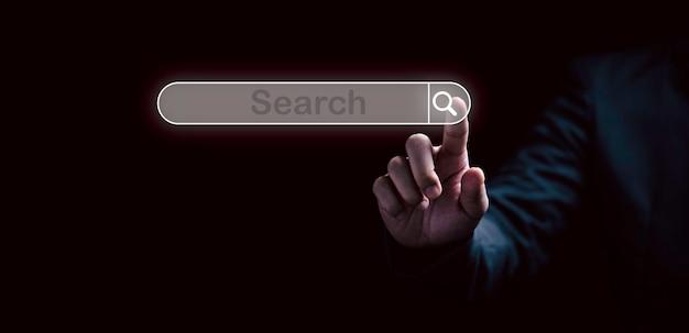 Die hand des mannes, die das suchsymbol für das virtuelle screening für das konzept der websuchmaschine berührt.