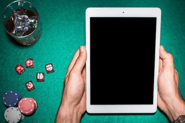 Die hand des mannes, die digitale tablette über der schürhakentabelle mit whiskyglas verwendet