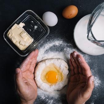 Die hand des mannes, die ei york über dem teig auf küchenarbeitsplatte bedeckt