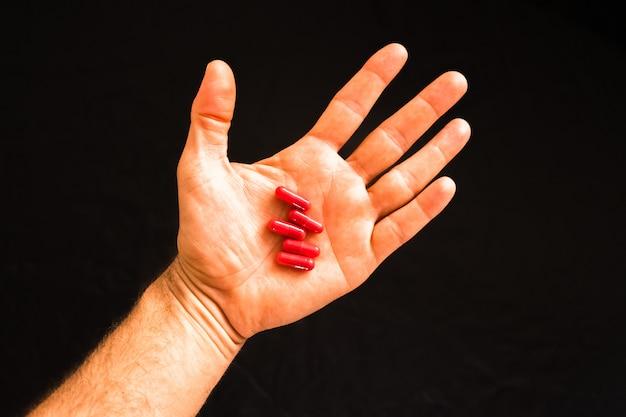Die hand des mannes, die eine handvoll medizinpillen hält, um suchtkrankheiten zu behandeln