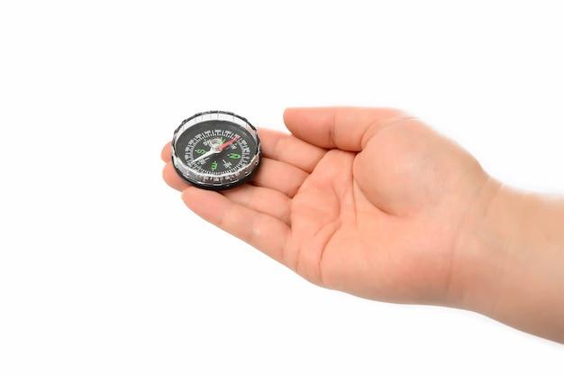Die hand des mannes, die einen kompass auf dem weißen hintergrund hält