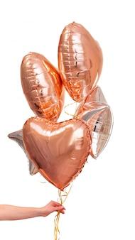 Die hand des mannes, die einige folienbälle hält, füllte mit helium