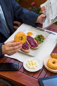 Die hand des mannes, die frühstück in der gaststätte isst
