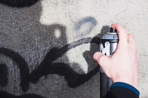 Die hand des mannes, die graffiti mit spray macht