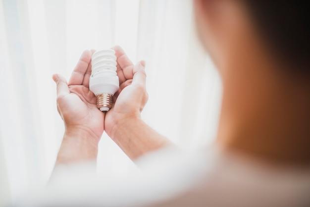 Die hand des mannes, die kompakte leuchtstoff glühlampe hält